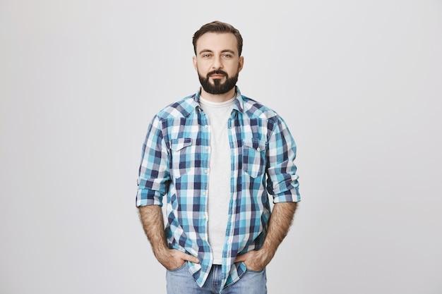 Homem adulto barbudo confiante com as mãos nos bolsos