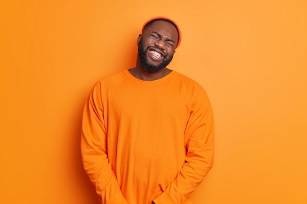 Homem adulto barbudo e triste e frustrado inclina a cabeça trinca os dentes tenta controlar suas emoções ruins sente muito choro infeliz de desespero usa chapéu jumper casual isolado sobre parede laranja