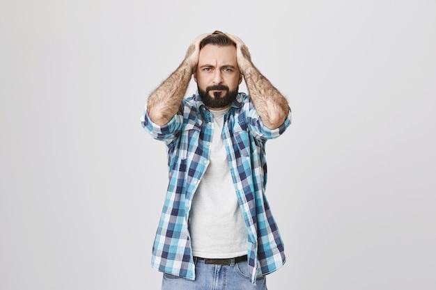 Homem adulto barbudo em dificuldades agarra a cabeça e parece aflito