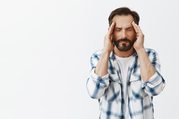 Homem adulto barbudo estressado posando
