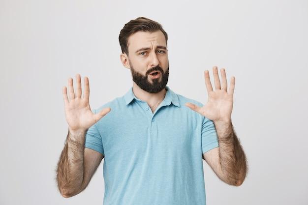 Homem adulto barbudo tentando acalmar a pessoa, levantando as mãos