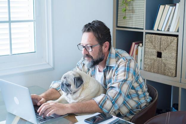 Homem adulto barbudo trabalhando em casa no escritório com seu cachorro amigo