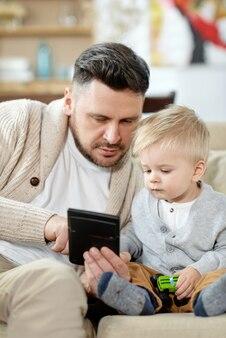 Homem adulto bonito acariciando no sofá com um menino curioso enquanto assistem o dispositivo juntos