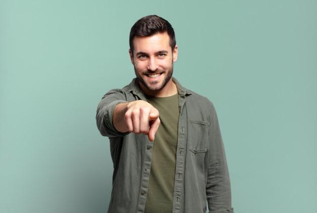 Homem adulto bonito apontando para a câmera com um sorriso satisfeito, confiante e amigável, escolhendo você