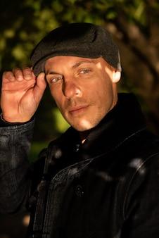 Homem adulto bonito com um casaco e um boné. foto de alta qualidade