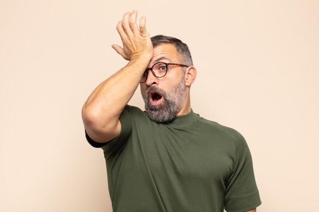 Homem adulto bonito erguendo a palma da mão na testa pensando, opa, depois de cometer um erro estúpido ou lembrar, sentindo-se idiota