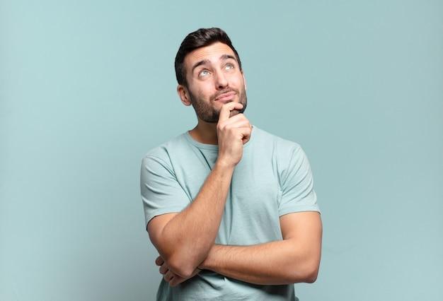 Homem adulto bonito jovem pensando, sentindo-se duvidoso e confuso, com diferentes opções, imaginando qual decisão tomar