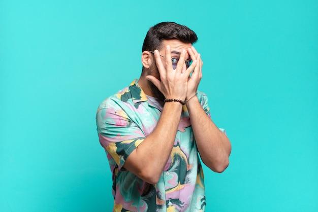 Homem adulto bonito jovem sentindo medo ou vergonha, espiando ou espiando com os olhos semicerrados com as mãos. conceito de férias