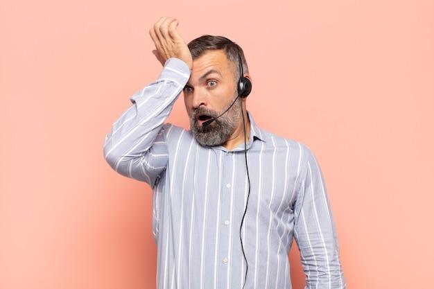Homem adulto bonito levantando a palma da mão na testa pensando, opa, depois de cometer um erro estúpido ou lembrar, sentindo-se idiota