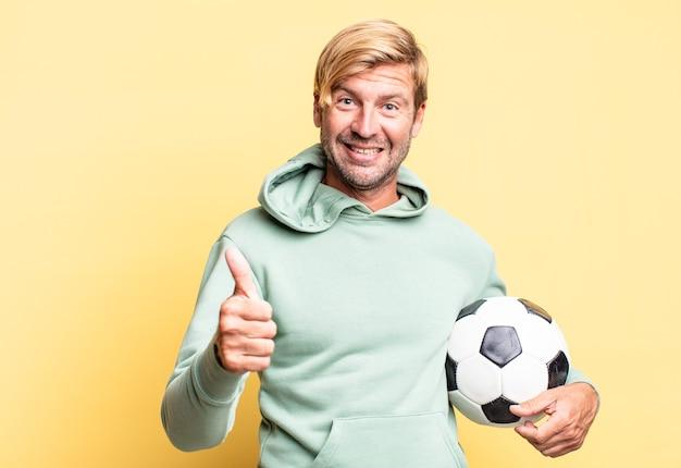 Homem adulto bonito loiro segurando uma bola de futebol