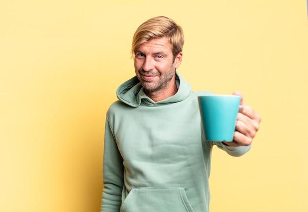 Homem adulto bonito loiro segurando uma xícara de café