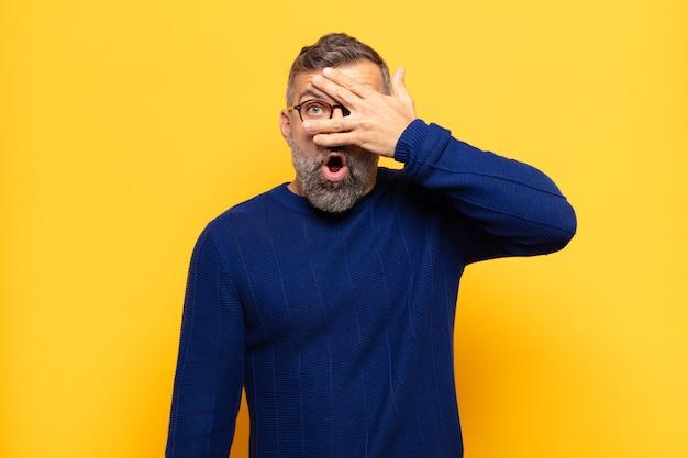 Homem adulto bonito parecendo chocado, assustado ou apavorado, cobrindo o rosto com a mão e espiando por entre os dedos