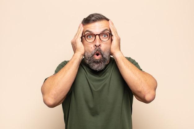 Homem adulto bonito parecendo desagradavelmente chocado, assustado ou preocupado, com a boca bem aberta e cobrindo as duas orelhas com as mãos