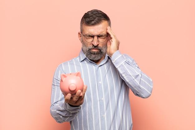 Homem adulto bonito parecendo estressado e frustrado, trabalhando sob pressão, com dor de cabeça e preocupado com problemas