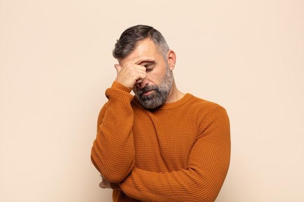 Homem adulto bonito parecendo estressado, envergonhado ou chateado, com dor de cabeça, cobrindo o rosto com a mão