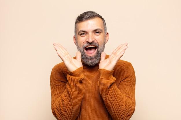 Homem adulto bonito parecendo feliz e animado, chocado com uma surpresa inesperada com as duas mãos abertas ao lado do rosto