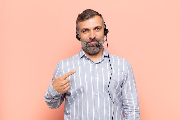 Homem adulto bonito parecendo orgulhoso, confiante e feliz, sorrindo e apontando para si mesmo ou fazendo o primeiro sinal