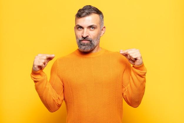 Homem adulto bonito parecendo orgulhoso, positivo e casual apontando para o peito com as duas mãos
