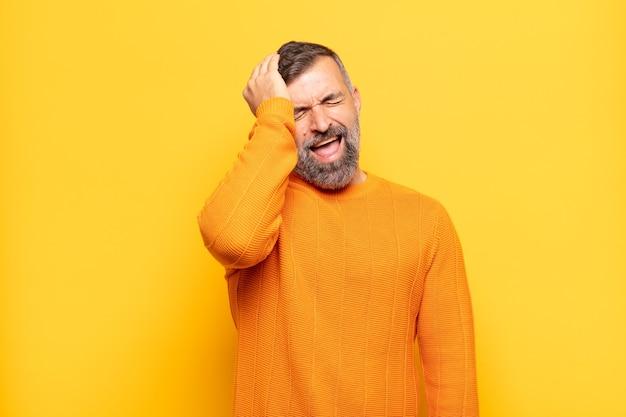 Homem adulto bonito rindo e batendo na testa