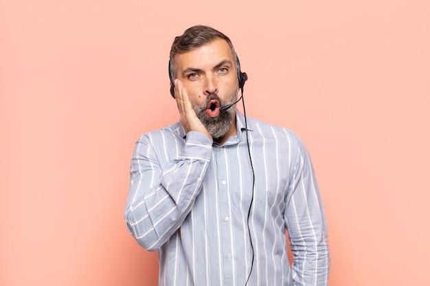 Homem adulto bonito se sentindo chocado e surpreso, com a boca aberta e a boca aberta
