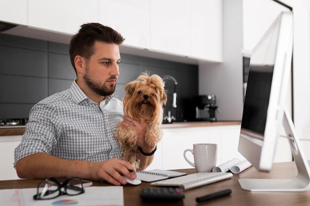 Homem adulto bonito segurando animal de estimação enquanto trabalha