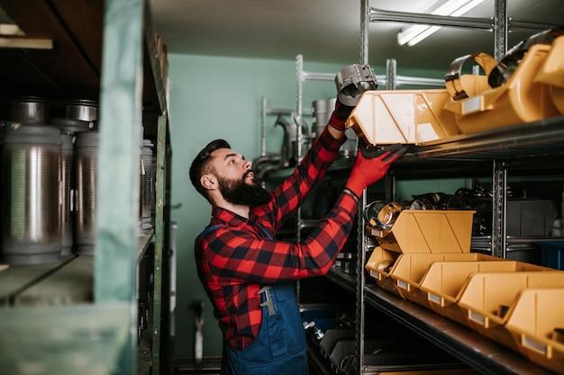 Homem adulto bonito, trabalhando no depósito de peças sobressalentes de carros e caminhões.