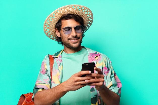 Homem adulto bonito turista indiano vestindo feno e uma bolsa de couro e usando seu celular