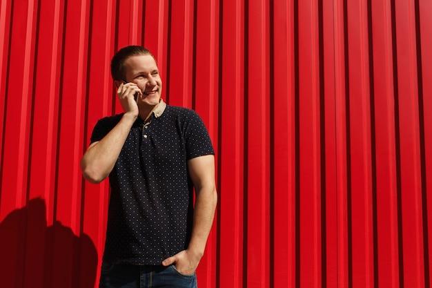 Homem adulto bonito usando seu telefone celular, falando sobre fundo vermelho, com espaço livre. jovem feliz em cima de fundo parede vermelha com telefone móvel