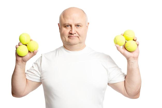 Homem adulto careca com bolas de tênis nas mãos. isolado em um fundo branco.