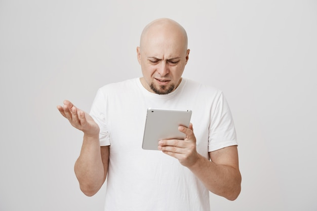 Homem adulto careca confuso olhando perplexo para tablet digital