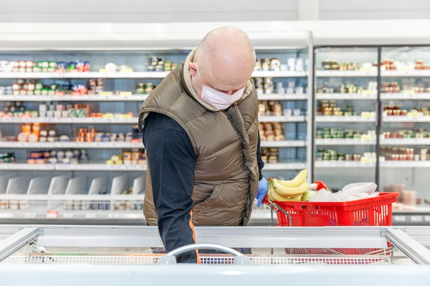 Homem adulto careca em uma máscara médica e luvas escolhe alimentos congelados em um supermercado. auto-isolamento e precauções durante a pandemia de coronavírus.