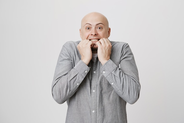 Homem adulto careca preocupado roendo as unhas