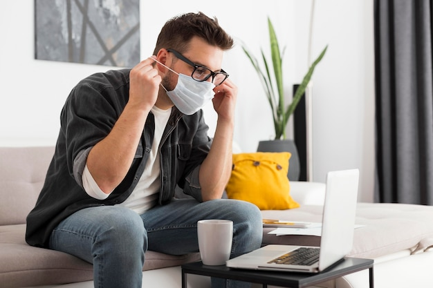 Homem adulto casual usando máscara facial em casa