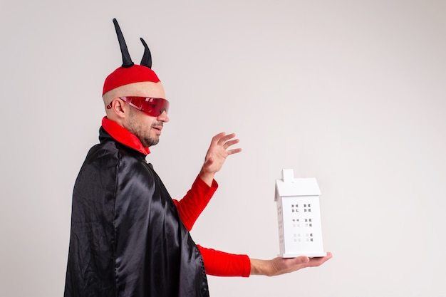 Homem adulto caucasiano com fantasia de halloween com edifício decorativo nas mãos, isolado no branco.