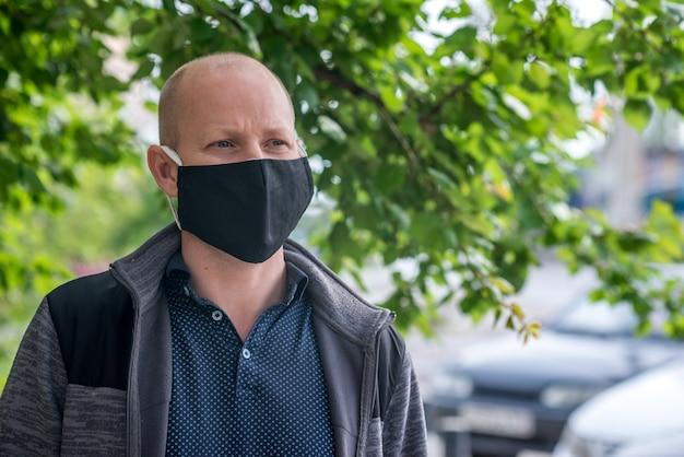 Homem adulto caucasiano em máscara protetora preta está caminhando um ao longo da rua vazia e falando no telefone. comportamento seguro durante a pandemia de quarentena e coronavírus.