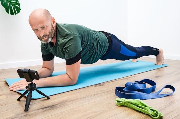 Homem adulto caucasiano em roupas esportivas, fazendo uma prancha no tapete na frente de um smartphone durante um treino online.