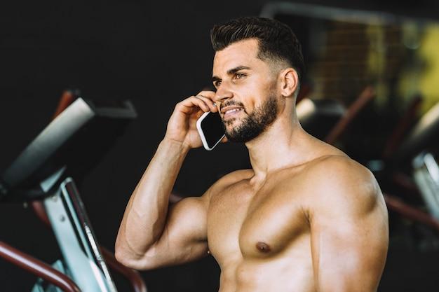 Homem adulto, caucasiano, forte, falando com o celular em uma academia