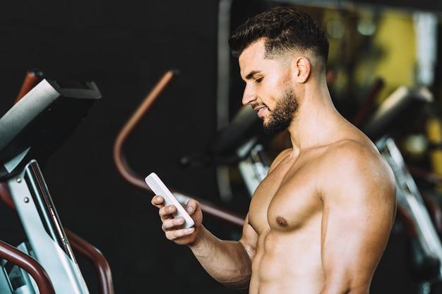 Homem adulto, caucasiano, forte, usando um celular em uma academia