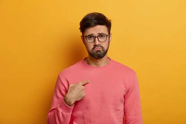 Homem adulto chateado e desapontado aponta para si mesmo, descontente por ter sido escolhido para punir