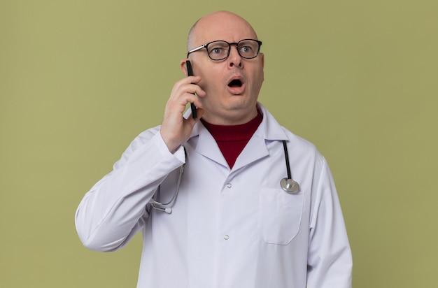 Homem adulto chocado com óculos e uniforme de médico com estetoscópio falando ao telefone