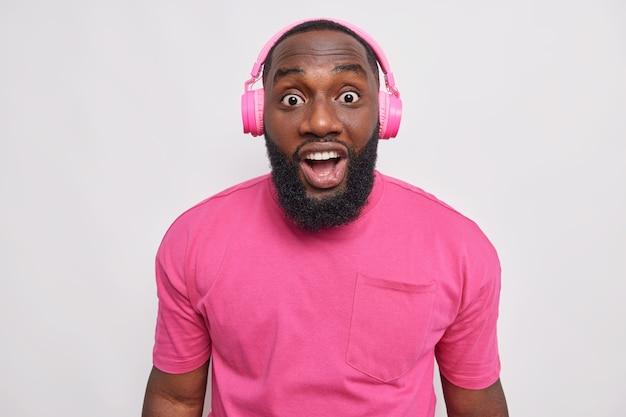 Homem adulto chocado e barbudo não consegue acreditar que seus olhos ficam de queixo caído enquanto a pele escura ouve notícias incríveis no rádio via fones de ouvido vestido com uma camiseta rosa isolada sobre a parede branca