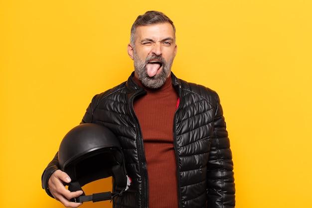 Homem adulto com atitude alegre, despreocupada, rebelde, brincando e mostrando a língua, se divertindo