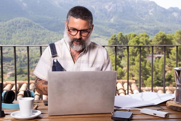 Homem adulto com barba, sentado com um laptop, trabalhando no terraço ao ar livre.