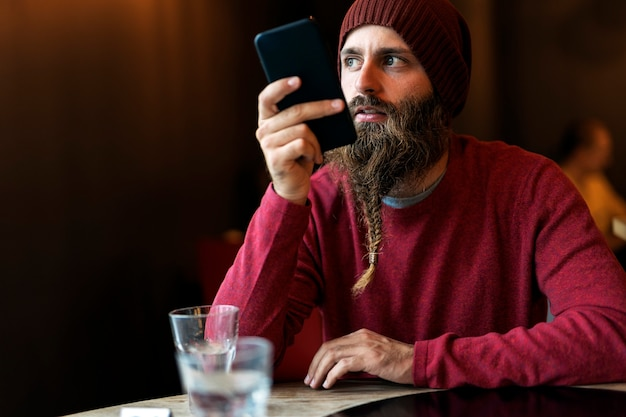 Homem adulto com barba trançada enviando uma voz com o celular e tomando uma xícara de café