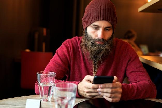 Homem adulto com barba trançada sentado em um café com um laptop, tomando uma xícara de café enquanto digita no telefone