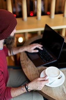 Homem adulto com barba trançada sentado no café, tomando uma xícara de café enquanto digita no laptop