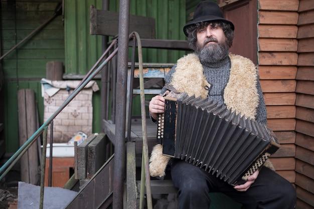 Homem adulto com cabelo encaracolado, barba e chapéu