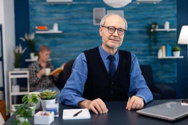 Homem adulto com cabelo grisalho olhando pensativo para a câmera usando óculos