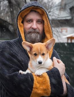 Homem adulto com cachorrinho corgi em roupas kozy no quintal de sua casa no outono