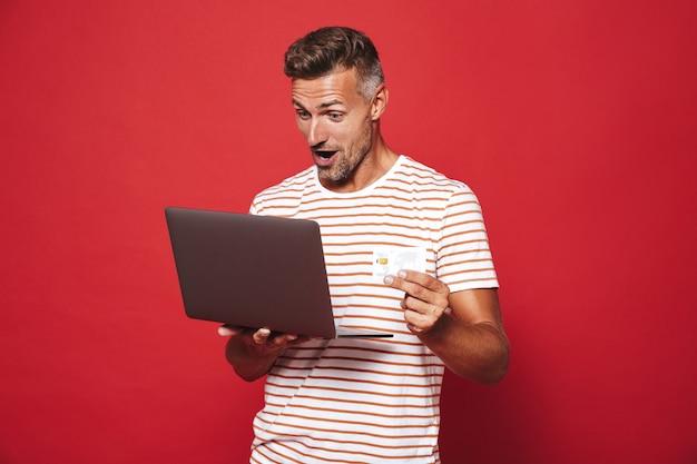 Homem adulto com camiseta listrada sorrindo enquanto segura o cartão de crédito e o laptop isolado no vermelho